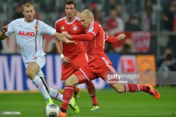 Arjen Robben of Munich's and Ragnar Klavan of Augsburg vie for the ball during the soccer Bundesliga match FC Bayern Munich vs FC Augsburg in the...