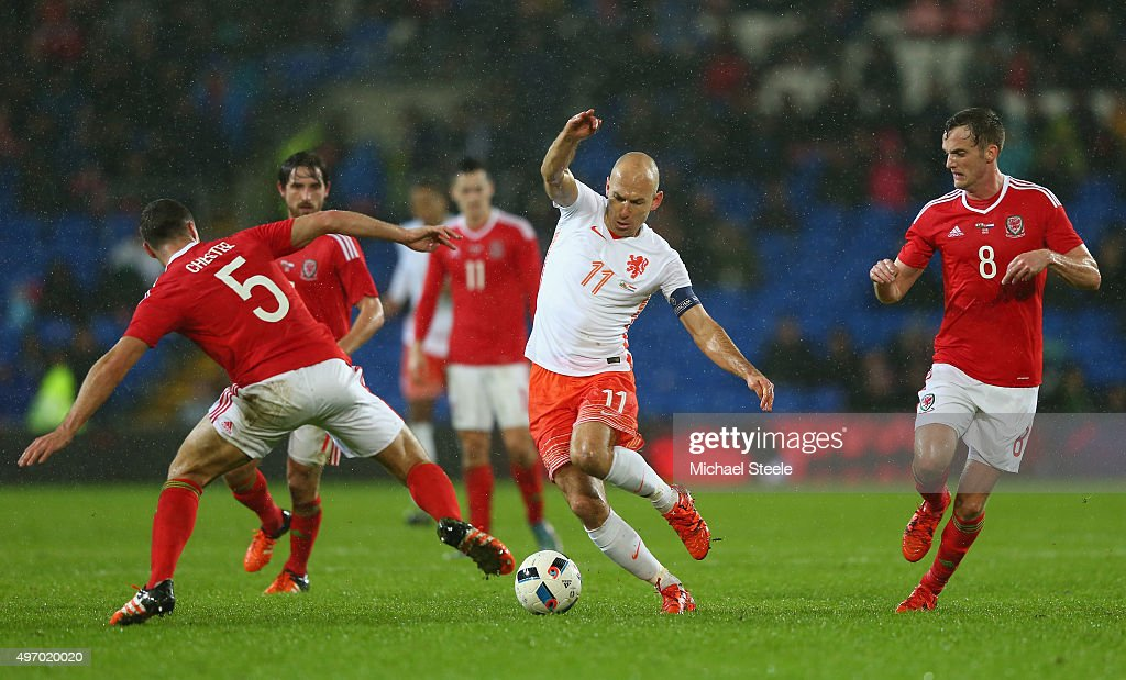 Arjen Robben of Netherlands is challenged by James Chester (L) and Andy King (R) during the international friendly match between Wales and Netherlands at Cardiff City Stadium on November 13, 2015 in Cardiff, Wales.
