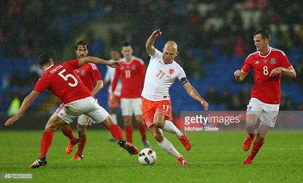 Arjen Robben of Netherlands is challenged by James Chester and Andy King during the international friendly match between Wales and Netherlands at...