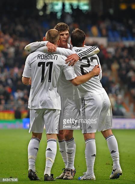Arjen Robben of Real Madrid celebrates with Klaas Jan Huntelaar and Rafael Van Der Vaart after scoring Real's third goal against Osasuna during the...