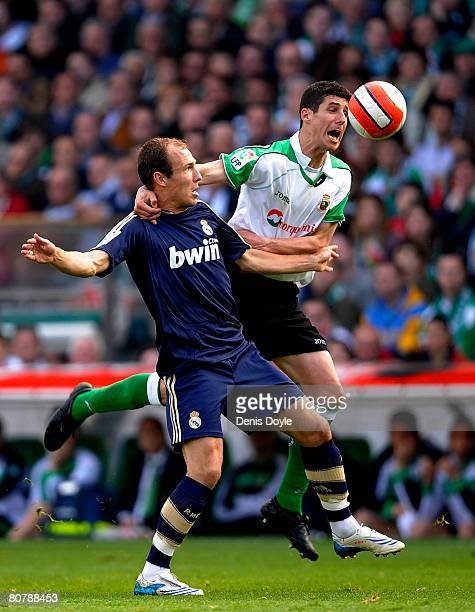 Arjen Robben of Real Madrid is tackled by Jose Moraton of Racing Santander during the Liga match between Racing Santander and Real Madrid at the El...