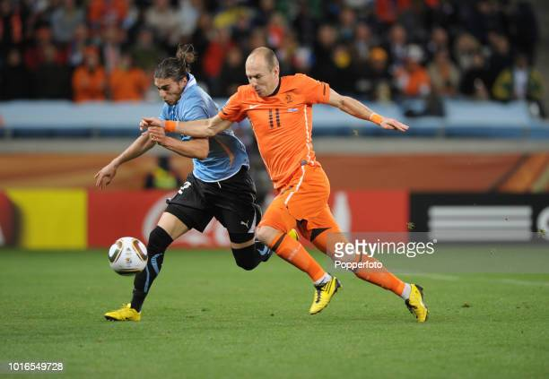 Arjen Robben of the Netherlands and Martin Caceres of Uruguay in action during the 2010 FIFA World Cup Semi Final match between Uruguay and the...