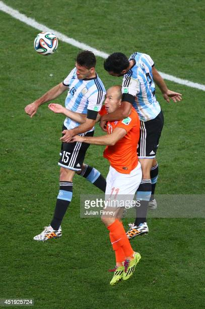 Arjen Robben of the Netherlands goes up for a header against Martin Demichelis and Ezequiel Garay of Argentina during the 2014 FIFA World Cup Brazil...