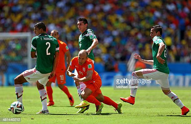 Arjen Robben of the Netherlands is challenged by Hector Herrera of Mexico as teammate Francisco Javier Rodriguez controls the ball during the 2014...