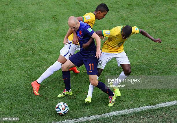 Arjen Robben of the Netherlands is challenged by Luiz Gustavo and Ramires of Brazil during the 2014 FIFA World Cup Brazil Third Place Playoff match...