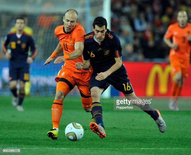 Arjen Robben of the Netherlands is challenged by Sergio Busquets of Spain during the FIFA World Cup Final at the Soccer City Stadium on July 11 2010...