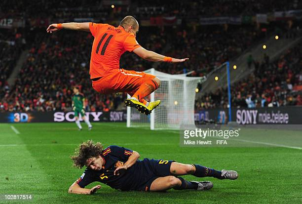 Arjen Robben of the Netherlands jumps over the challenge by Carles Puyol of Spain during the 2010 FIFA World Cup South Africa Final match between...