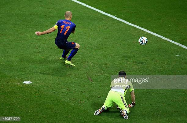 Arjen Robben of the Netherlands shoots and scores his second goal the team's fifth as goalkeeper Iker Casillas of Spain looks on during the 2014 FIFA...