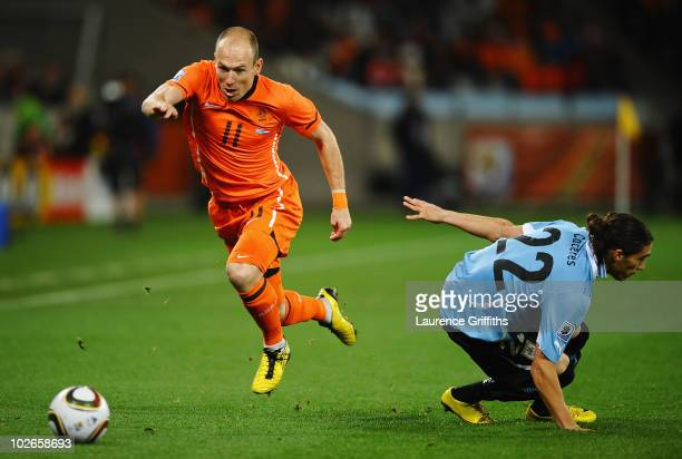 Arjen Robben of the Netherlands takes the ball past Martin Caceres of Uruguay during the 2010 FIFA World Cup South Africa Semi Final match between...