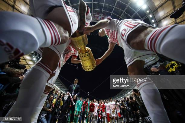 Arjen Robben Rafinha and Franck Ribery of Muenchen celebrate with the DFB Pokal following their team's victory in the DFB Cup final between RB...