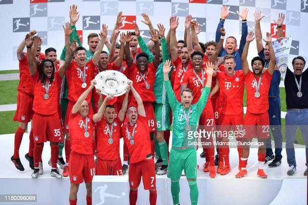 Arjen Robben Rafinha and Franck Ribéry of FC Bayern München lift the title trophy in celebration following the Bundesliga match between FC Bayern...