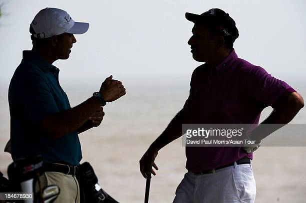 Arjun Atwal of India and Jeev Milkha Singh of India talk during the practice round of the Venetian Macau Open on October 15 2013 at the Macau Golf...