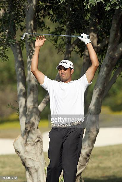 Arjun Atwal of India prepares to hit his second shot to the 18th green during the final round of the 2008 Johnnie Walker Classic held at The DLF Golf...