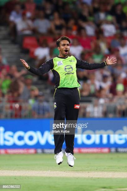 Arjun Nair of the Thunder celebrates taking the wicket of Johan Botha of the Sixers during the Big Bash League match between the Sydney Thunder and...