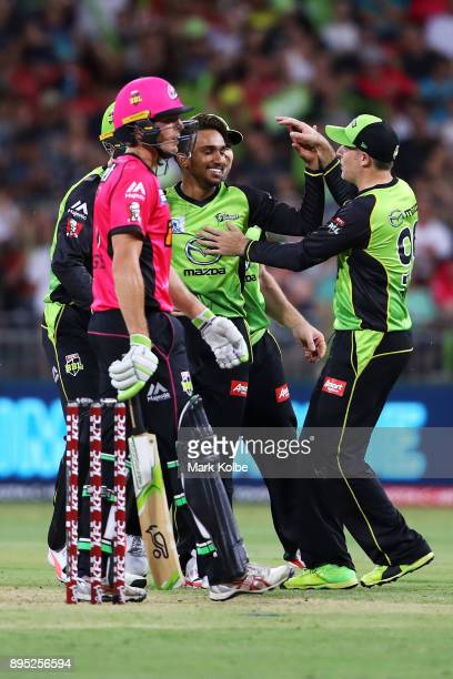 Arjun Nair of the Thunder celebrates with his team after taking the wicket of Moises Henriques of the Sixers during the Big Bash League match between...