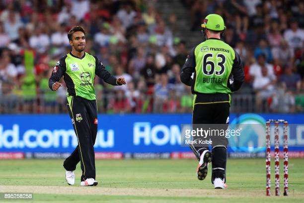 Arjun Nair of the Thunder celebrates with Jos Buttler after taking the wicket of Johan Botha of the Sixers during the Big Bash League match between...