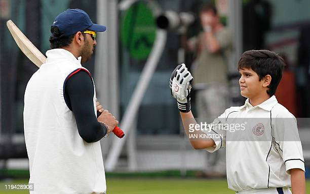 Arjun son of India's Sachin Tendulkar gestures to India's Yuvraj Singh during a training session at Lord's Cricket Ground in London on July 20 2011...