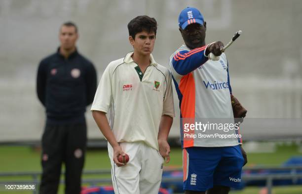 Arjun Tendulkar son of Sachin Tendulkar receives some instruction from England's bowling coach Ottis Gibson during an England training session before...