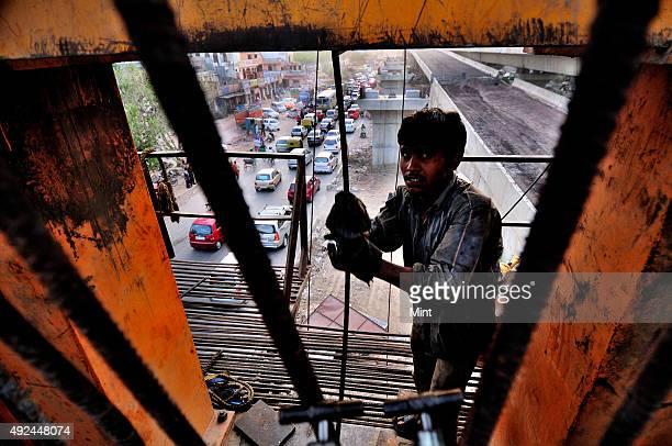 Arjun threading high strength wire in a segment of bridge on the bridge girder launcher on June 23 2012 in New Delhi India Sandblasting is a general...