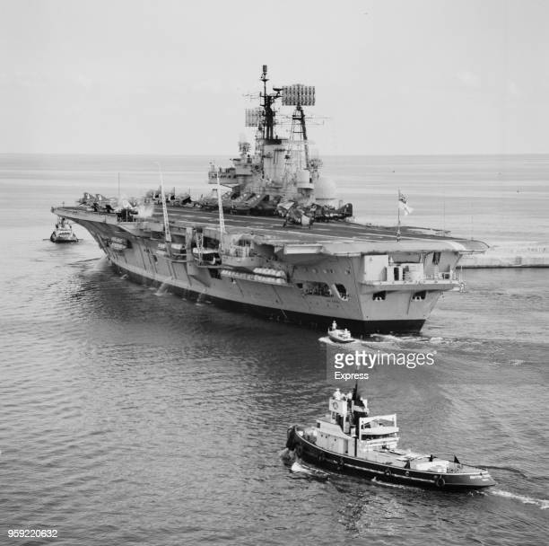 HMS Ark Royal Audaciousclass aircraft carrier of the Royal Navy is escorted by tugs as she leaves Malta Dockyard in the Grand Harbour Valletta Malta...
