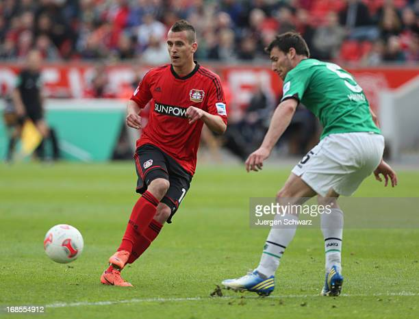 Arkadiusz Milik of Leverkusen kicks the ball beside Mario Eggimann of Hannover during the Bundesliga match between Bayer 04 Leverkusen and Hannover...
