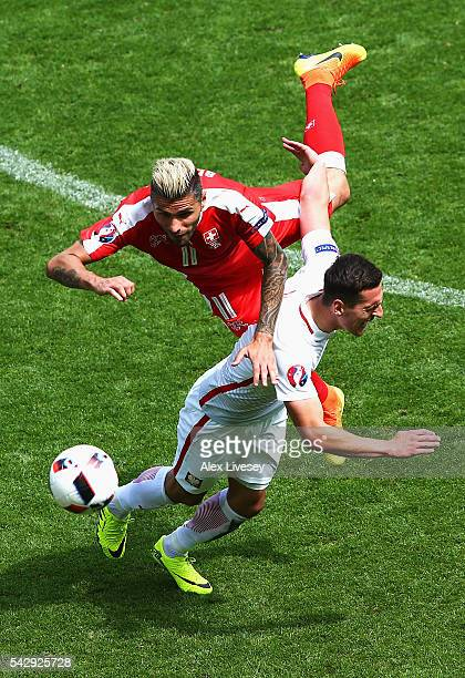Arkadiusz Milik of Poland and Valon Behrami of Switzerland compete for the ball during the UEFA EURO 2016 round of 16 match between Switzerland and...