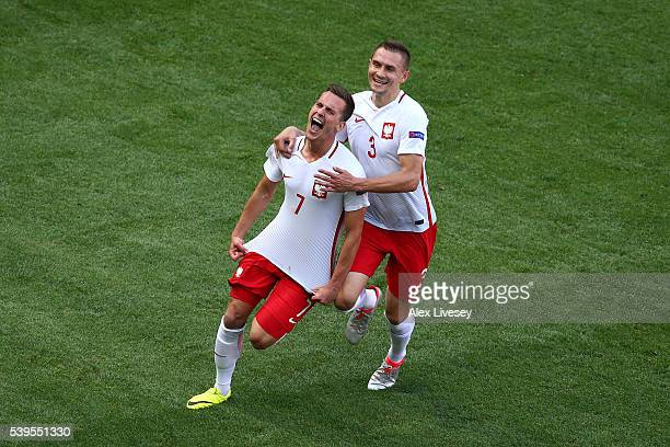 Arkadiusz Milik of Poland celebrates scoring his team's first goal with his team mates Artur Jedrzejczyk during the UEFA EURO 2016 Group C match...
