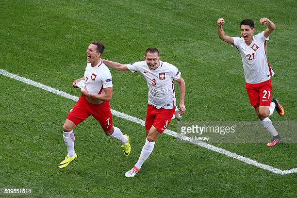 Arkadiusz Milik of Poland celebrates scoring his team's first goal with his team mates Artur Jedrzejczyk and Bartosz Kapustka during the UEFA EURO...