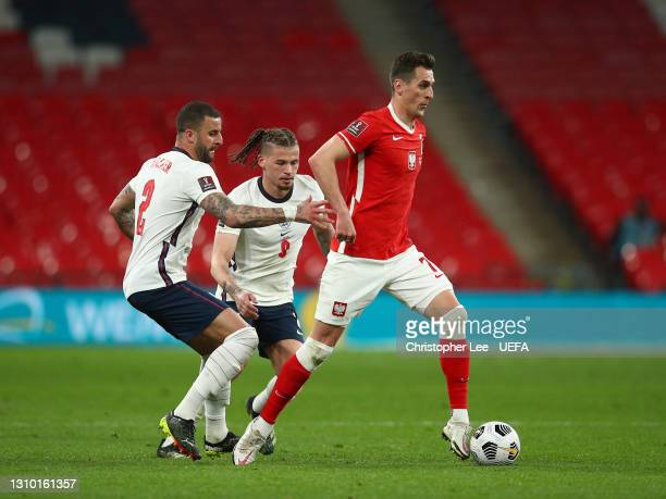 Arkadiusz Milik of Poland runs with the ball whilst under pressure from Kyle Walker and Kalvin Phillips of England during the FIFA World Cup 2022...