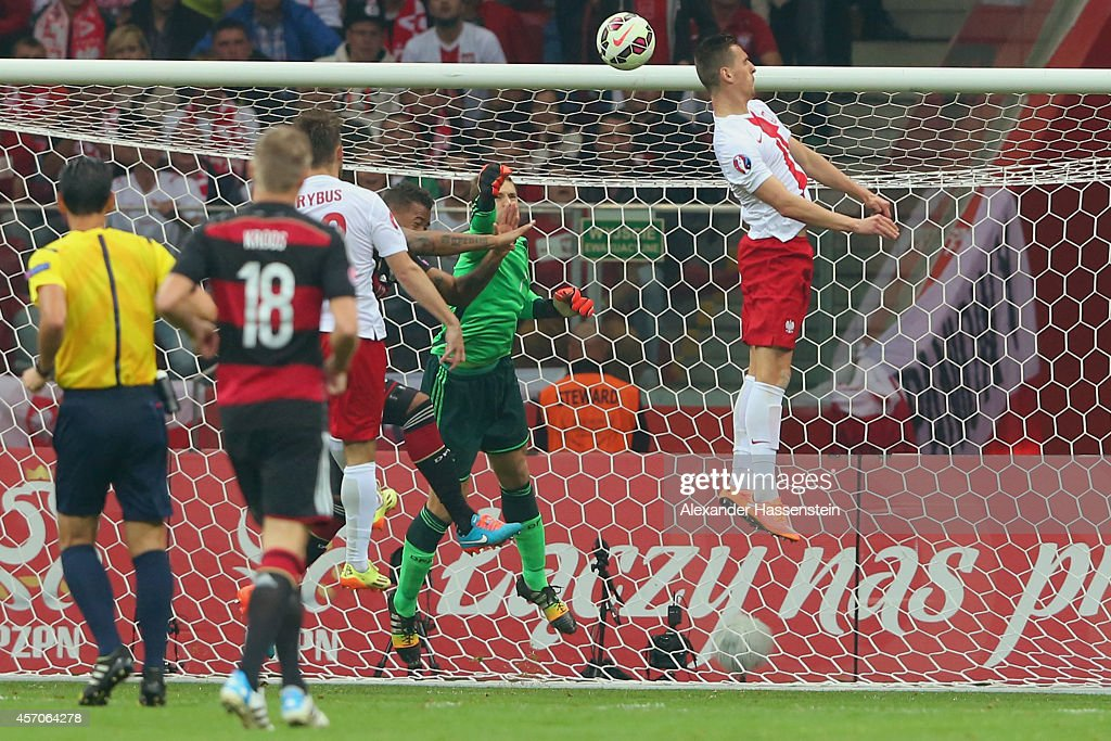 Arkadiusz Milik (R) of Poland scores the opening goal against Manuel Neuer, keeper of Germany during of the EURO 2016 Group D qualifying match between Poland and Germany at Narodowy Stadium on October 11, 2014 in Warsaw, Poland.