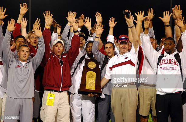 Arkansas coach John McDonnell celebrates with team after the Razorbacks won their third title in a row in the NCAA Track & Field Championships at...