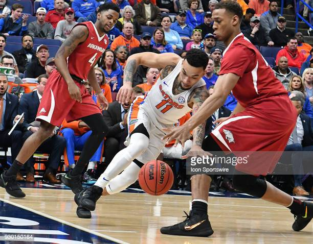 Arkansas forward Orlando Cook tries to keep the ball away from Florida guard Chris Chiozza during a Southeastern Conference Basketball Tournament...