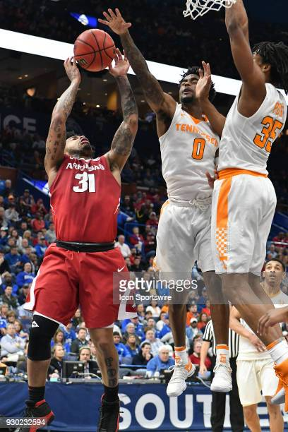 Arkansas guard Anton Beard attempts a shot with Tennessee guard Jordan Bone and Tennessee forward Yves Pons defending during a Southeastern...