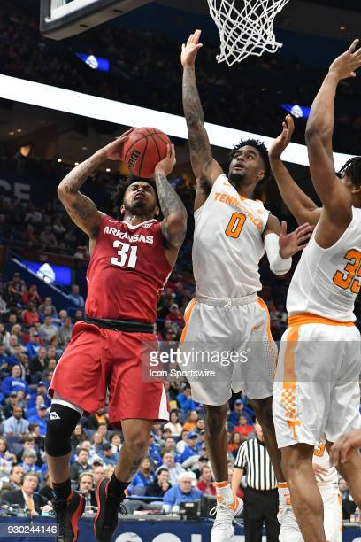 Arkansas guard Anton Beard puts up a shot over Alabama forward Donta Hall and Tennessee forward Yves Pons during a Southeastern Conference Basketball...