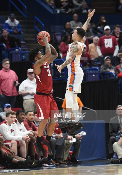 Arkansas guard Anton Beard puts up a shot over Florida forward Kevarrius Hayes during a Southeastern Conference Basketball Tournament game between...