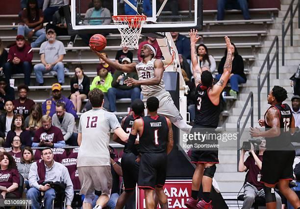 Arkansas Little Rock Trojans forward Ben Marcus scoops a shot under the basket during an NCAA basketball game between the University of Louisiana at...