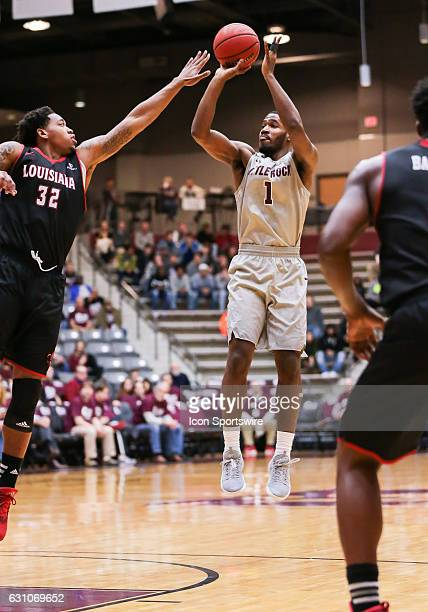 Arkansas Little Rock Trojans forward Jalen Jackson shoots over Louisiana Lafayette Ragin Cajuns forward Bryce Washington during an NCAA basketball...