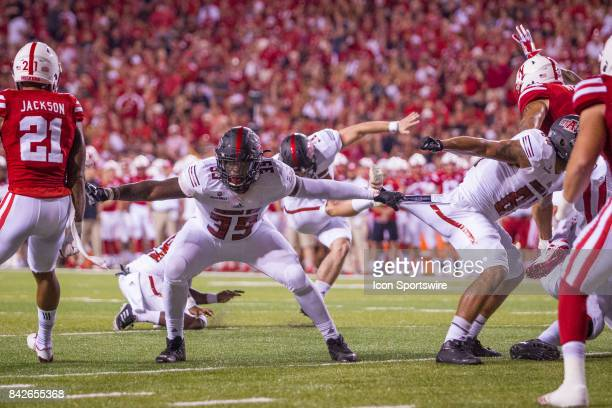 Arkansas State Red Wolves defensive end Dajon Emory holding on to Arkansas State Red Wolves tight end Jonah Hill pants while blocking for a field...