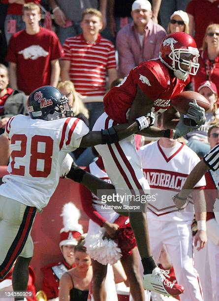 Arkansas wide receiver Marcus Monk attempts to haul in a pass against Ole Miss defensive back Nate Banks at Donald W Reynolds Razorback Stadium in...