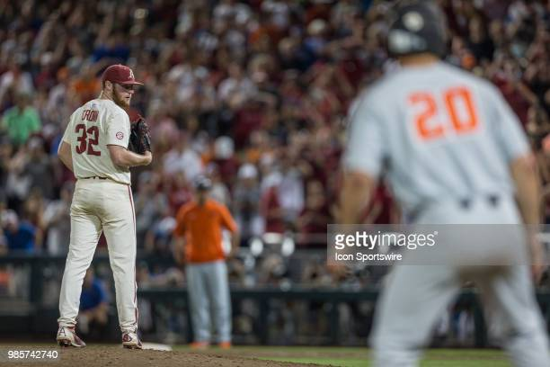 Arkansas's Matt Cronin looks at Oregon State's Zach Clayton that on third base in the ninth during the second game of the finals in the College World...