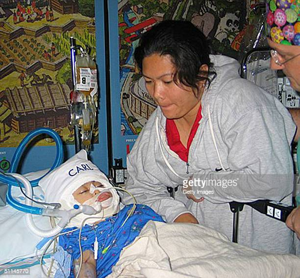 Arlene Aguirre looks at her son Carl at The Children's Hospital August 4 2004 at Montefiore Medical Center in the Bronx New York Twoyearold Filipino...