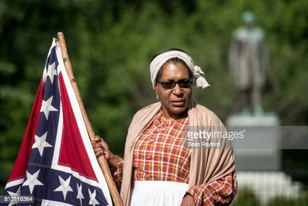 Arlene Barnum of Stewart OK holds a Confederate flag in front of the Ben Tillman Statue at the South Carolina Statehouse on July 10 2017 in Columbia...