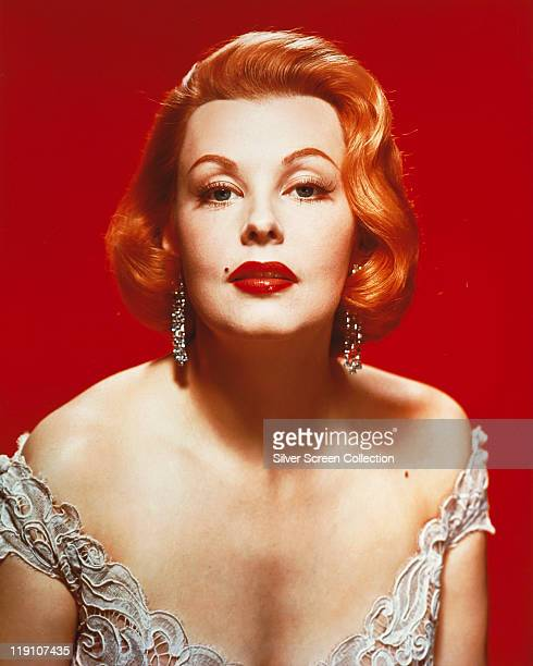 Arlene Dahl US actress wearing a lowcut top in a studio portrait against a red background circa 1960