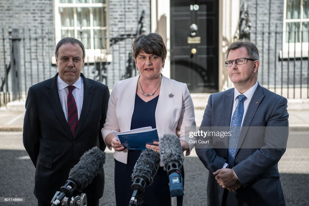 Arlene Foster (C), the leader of Northern Ireland's Democratic Unionist Party, party deputy leader, Nigel Dodds (L) and MP Jeffrey Donaldson (R), speak to the media as they leave after meeting Prime Minister Theresa May in 10, Downing Street on June 26, 2017 in London, England. The Conservatives have reached a deal with the Democratic Unionists in which the Northern Ireland party will support Theresa May's minority government.
