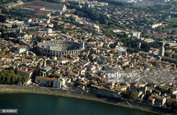 arles and roman arena on rhone river, france - amphitheatre stock photos and pictures