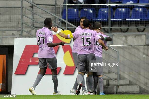 Arles' forward Franck Dja Dje DJe is congratulated by his teammates after scoring a goal during the French L1 football match Sochaux versus Arles on...