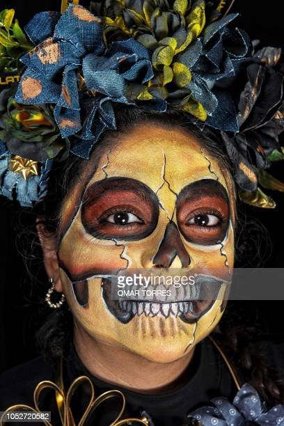Arlette Ortiz poses for a photograph disguised as 'Catrina' before the March of Catrinas organized by Body Paint group in Mexico City on October 21...