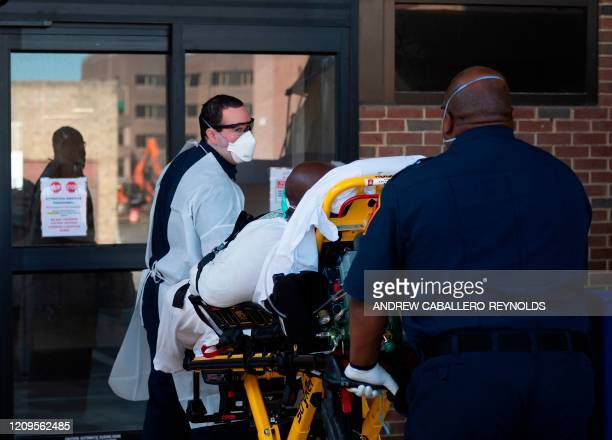 Arlington county Fire Department paramedic Ben Bieber and Brian Holmes unload a patient with respiratory issues from an ambulance at a hospital in...