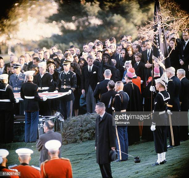 Arlington National Cemetery: Coffin of President Kennedy is lowered into its grave, Mrs. Kennedy stands next to her brother-in-law, Robert F. Kennedy.