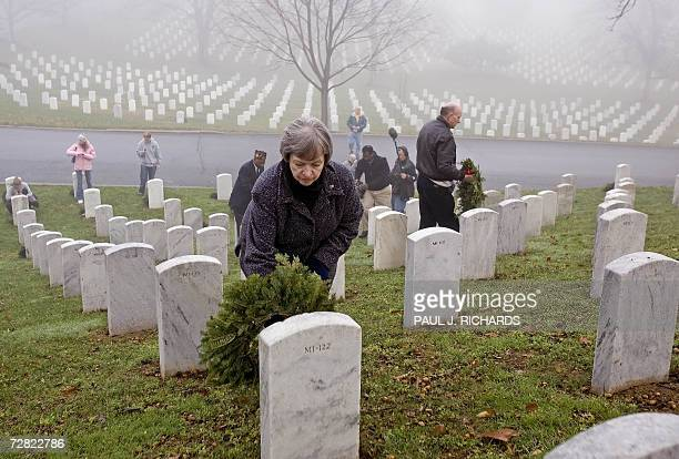 Bridget Hughes from Germany places one of 5000 donated Maine balsam fir holiday wreaths on some of the the 300000 grave stones with the help of...
